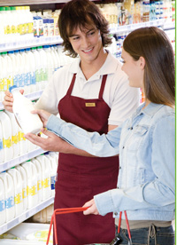 Grocery clerk showing a woman a half gallon milk label