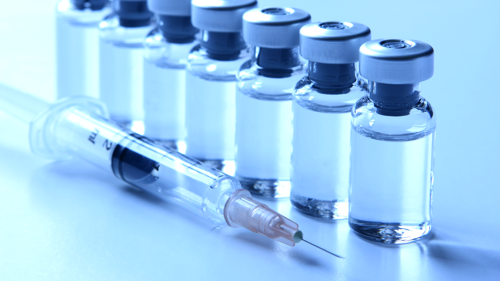 a row of seven small glass medical vials containing clear liquid and a medical syringe used for injecting vaccines