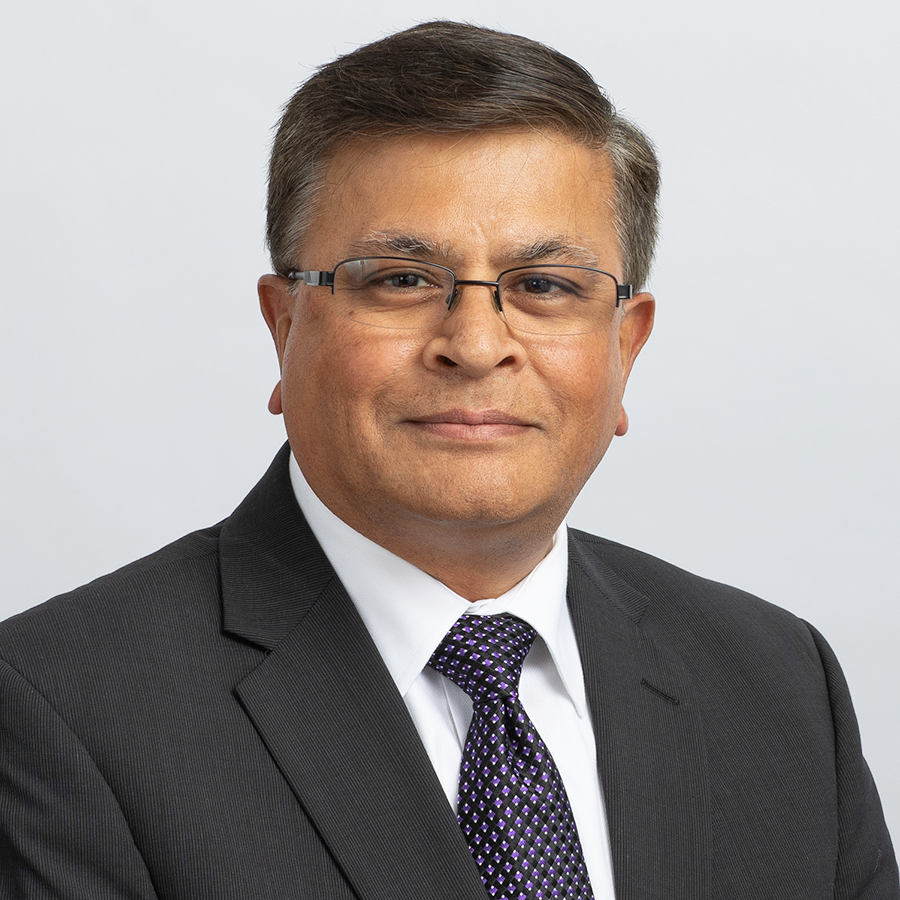 Portrait of Vid Desai, FDA's Chief Technology Officer, wearing a dark suit, dark tie, white shirt, glasses, and smiling while looking at the camera