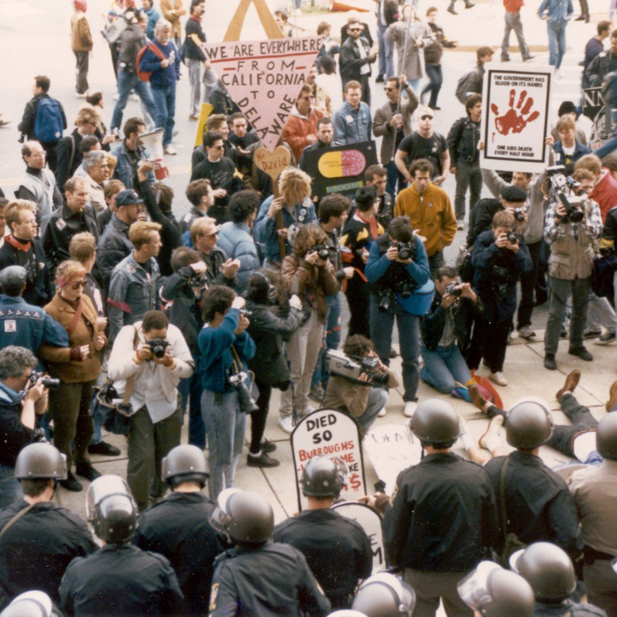 Photographers documenting a crowd of people outside FDA headquarters protesting the agency's lack of action in response to HIV/AIDS epidemic in 1988.