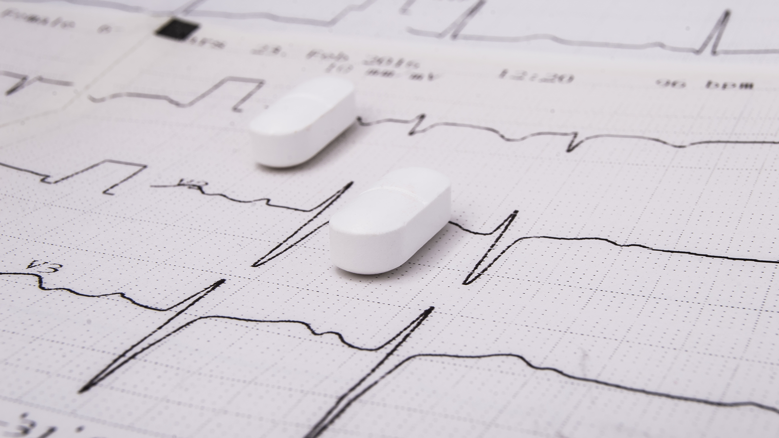 White pills on paper with EKG trace