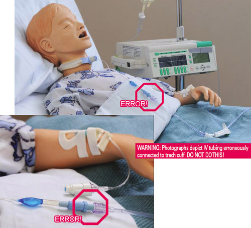 IV tubing erroneously connected to trach cuff on mannequin laying in hospital bed.