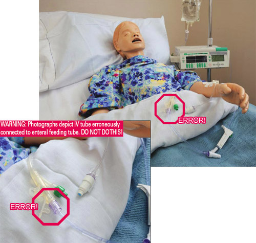 IV tubing erroneously connected to enteral feeding tube on a mannequin in hospital bed.