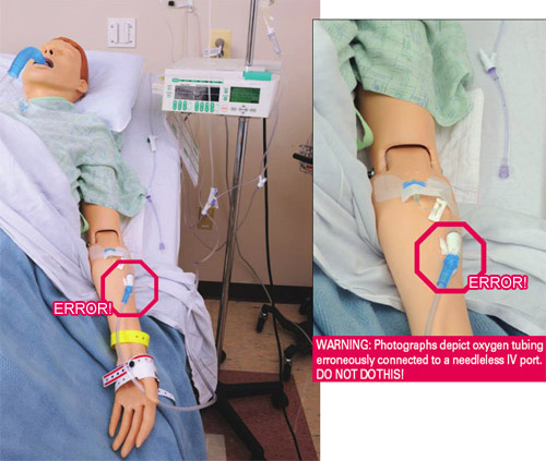 Oxygen tubing erroneously connected to a needleless IV port on mannequin arm