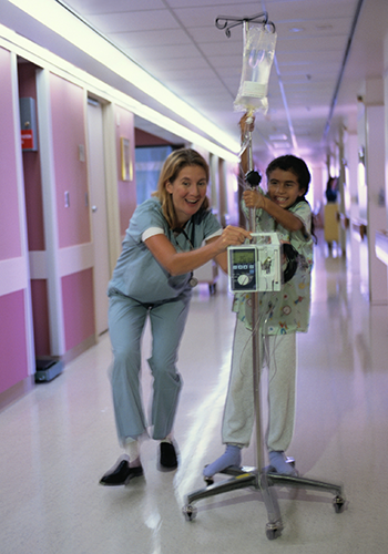 Child patient playing in hospital hallway with nurse