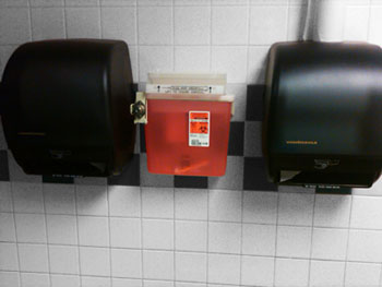 Sharps disposal container mounted in a restroom between two towel dispensers