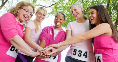 group of women wearing pink shirts holding hands together
