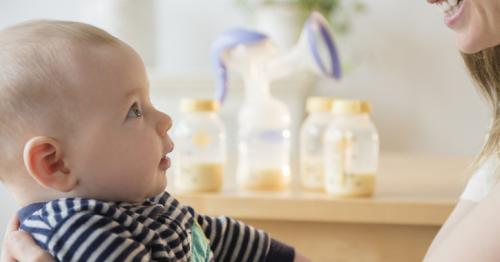 photo of mother holding infant with breast milk bottles in the background