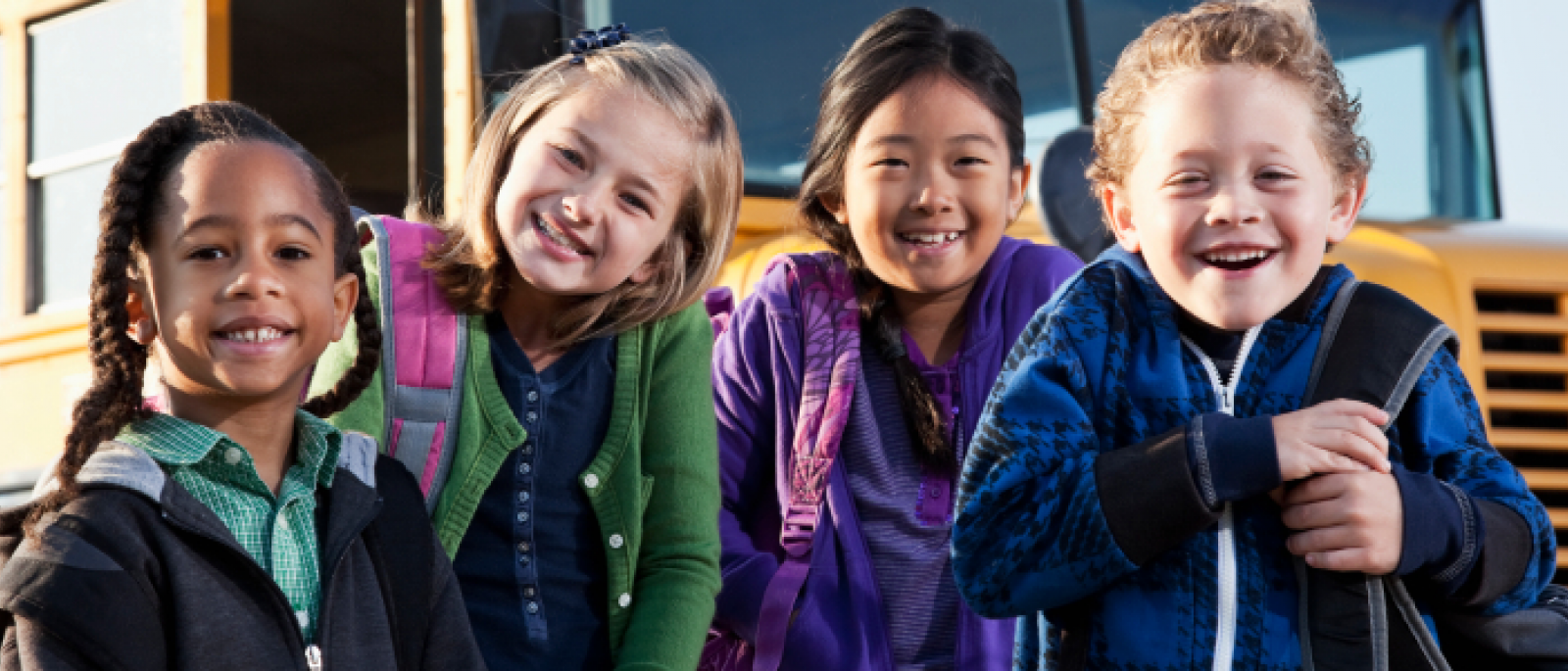 Four smiling children standing in front of a school bus.