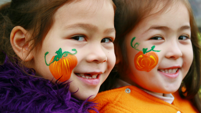 two smiling young girls wearing halloween costumes with pumpkins painted on their faces