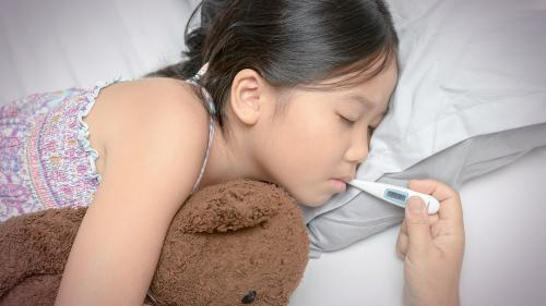 A young female child in bed with her eyes closed hugging a teddy bear while an adult's hand holds a thermometer in her mouth to check her temperature.