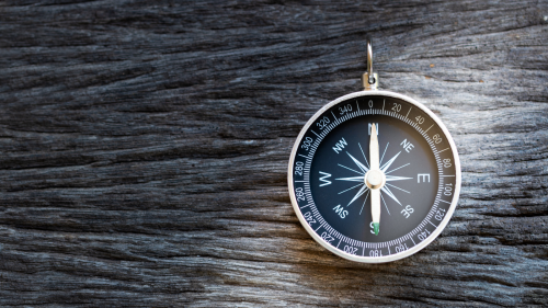 Compass on wooden background, representing the concept of guidance