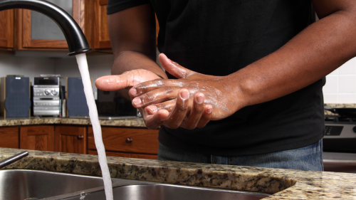 man washing hands with soap and water at kitchen sink