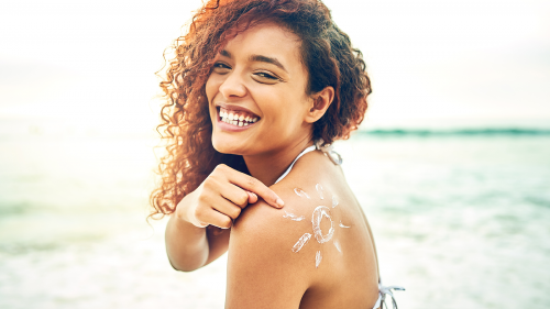 young woman on at the beach in a bikini, looking at the camera and smiling while pointing at a stylized drawing of a sun on her shoulder made with sunscreen