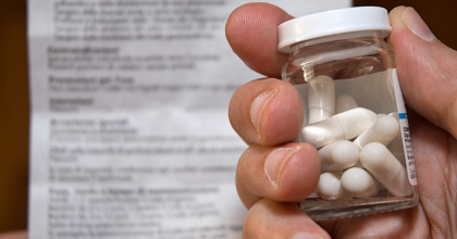 Person holding a glass bottle of pills and a medication guide