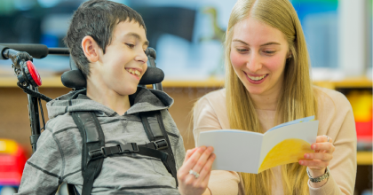 Smiling child in wheel chair looking at pamphlet held by a woman