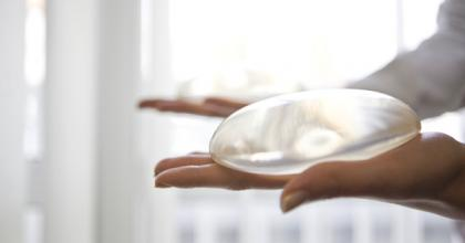 Photograph of a woman holding a breast implant