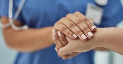 Closeup shot of a nurse holding a patient's hand in comfort in a hospital