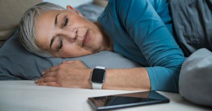 woman sleeping with smart watch next to smart phone
