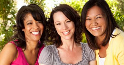 three women of different ethnicity, smiling