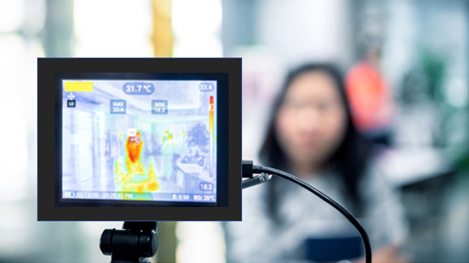 Figure one: A picture of an infrared thermal camera pointed at a woman standing by herself in a public space. The camera displays her thermal image on the camera screen. Her face is shown on the screen in a reddish orange color indicating her skin has a higher surface temperature than her clothing displayed as yellow and the distant background displayed as gray. The temperature displayed on the screen as 31.7o Celsius.