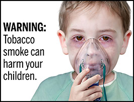 "A rectangular cigarette health warning with a white background and black text that reads: ""WARNING: Tobacco smoke can harm your children."" To the right of the text is a photorealistic illustration showing the head and shoulders of a young boy (aged 8-10 years) wearing a hospital gown and receiving a nebulizer treatment for chronic asthma resulting from secondhand smoke exposure. The warning is surrounded by a black outline."