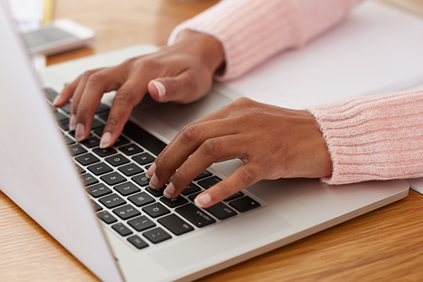 A woman typing on a laptop keyboard
