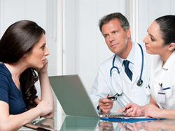 Female patient talking with a doctor and a nurse.