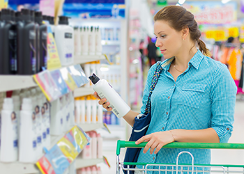 young woman reading label on cosmetic bottle in store (350 x 250)