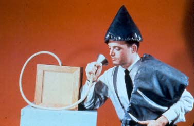 A man is sitting down wearing a cone shaped hat, holding a sash-like device over his left side, and he is holding a cone shaped device to his mouth.
