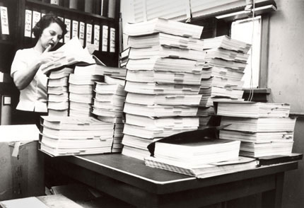 A woman looking over several binders of information housed on a lab table.