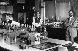 Three men in a laboratory (L to R): Rex Shiveley, L.B. Mears, and W.O. Emery
