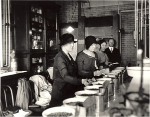 4 women standing behind a table looking at contents in bowls