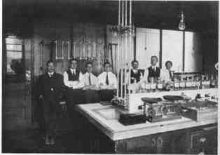 7 men behind a lab table.