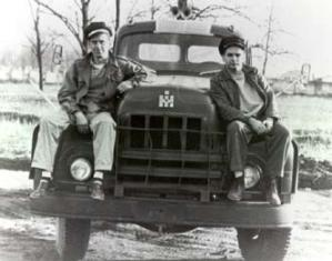 Two men sitting on top of a truck.