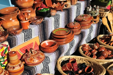 mexican pottery stall with different sized pottery lined up on shelves