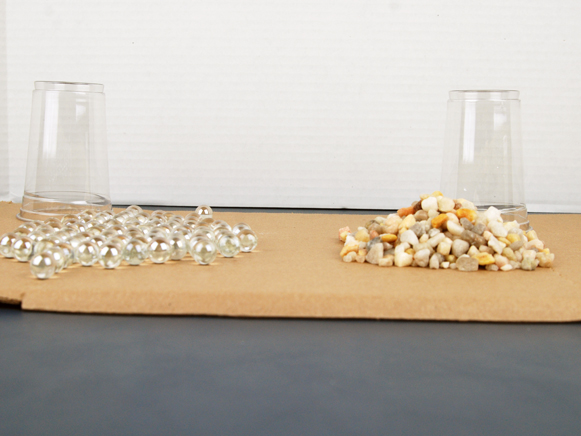 Cup of marbles and cup of rocks dumped on table