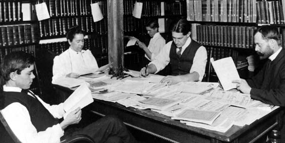 Four men and one woman seated in a library with journals spread on a table in front of them
