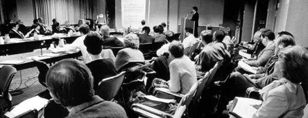 An advisory committee meeting: A man giving a presentation at a lecturn, committee members sitting around a conference table, and observers sitting in rows of chairs