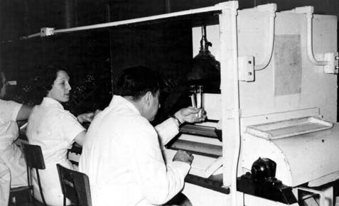 Man in a white lab coat seated at a piece of manufacturing equipment examining a vial with a woman looking on