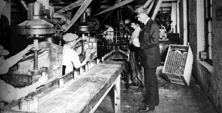 Two workers in a manufacturing plant packing bottles of product with a man in a suit and hat looking on