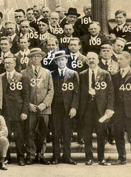 Group picture of men in suits, with a number appearing on each person (') s image. The man labeled 38 is highlighted.