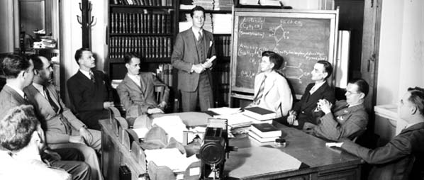 Nine men sitting around a conference table and one man standing in front of a backboard showing chemical diagrams