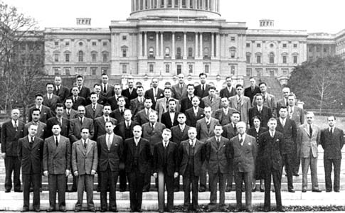 Group picture of men in suits, standing in front of the U.S. Capitol