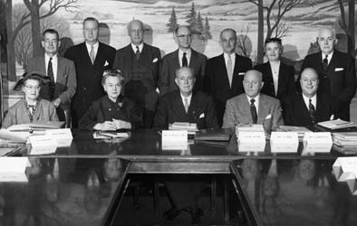 Group picture of three women and nine men gathered behind a conference table with stacks of paper in front of them
