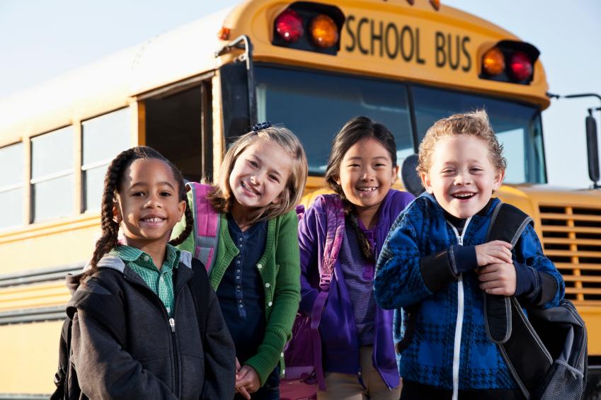 Children standing in front of school bus.