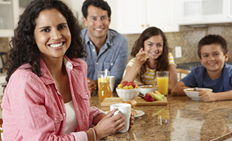 Latina eating breakfast with her husband and two children
