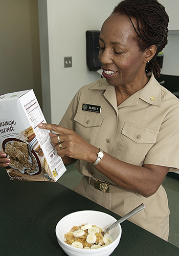 FDA nutritionist Shirley Blakely points out nutrition facts label on box of cereal (350x500)
