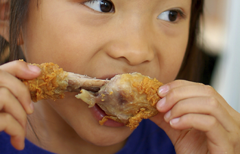 young girl eating fried chicken (350x224)