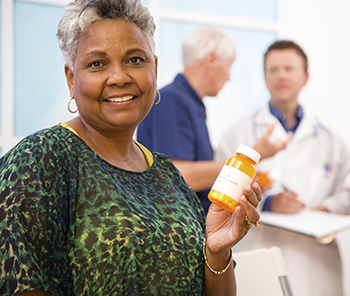 senior african-american woman holding pill bottle (350x296)